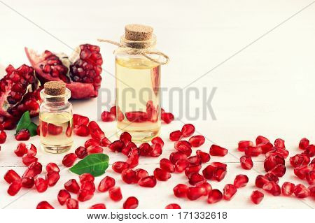 Pomegranate oil. Punica granatum ruby red fruit seeds, cosmetic vials. Facial nourishing oily extract.