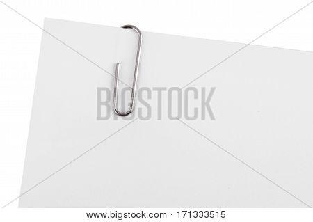 Paper clip on corner of white paper.