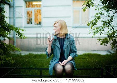Outdoor Portrait Of Young Blonde Woman, Wearing A Raincoat, Smoking Electronic Cigarette