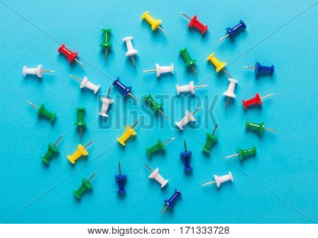 Colorful collection of Push pins in Grouping on blue background.