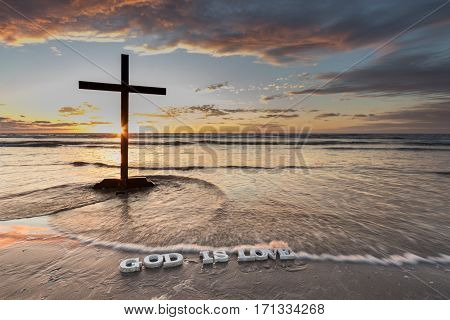 Black Cross on a beach with waves washing over the words 'God is Love' at sunset.