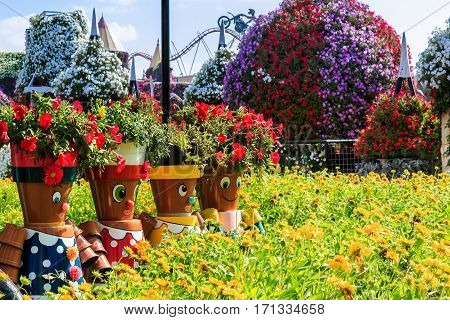 Dubai, UAE - January 5, 2017.   Dubai Miracle Garden - Dolls on the lawn in front of a flowerbed. Dubai Miracle Garden is the largest natural flower garden in the world