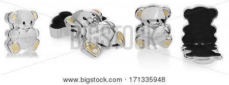 Silver box in the shape of a teddy bear to the first baby teeth. The Children souvenirs lined inside with black velvet. Ears and feet in yellow on a white background with slight reflection. Toy box opened and closed at different angles on a white backgrou