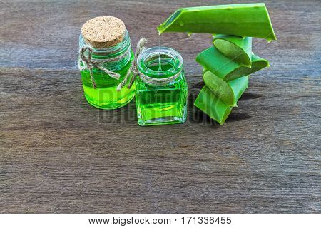 Slice Aloe Vera (Aloe barbadensis Mill.Star cactus Aloin Jafferabad or Barbados) and Aloe vera essential oil with gel in spoon on wooden