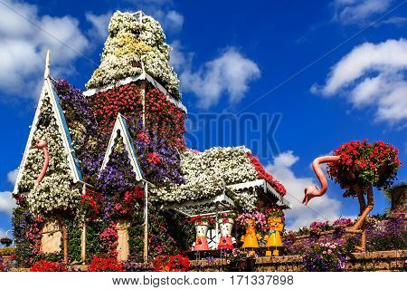 Dubai, UAE - January 5, 2017.   Dubai Miracle Garden - Floral house, dolls and ostrich on the background of clouds. Dubai Miracle Garden is the largest natural flower garden in the world