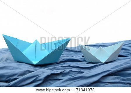 Blue paper boats, origami boats on blue texture