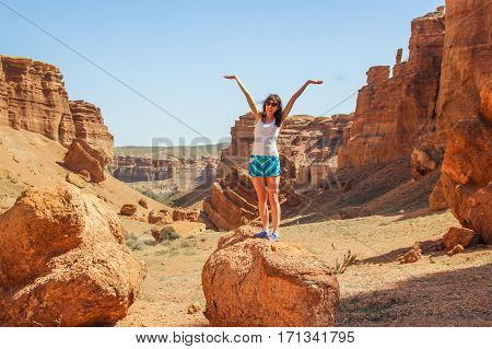 Happy young sporty woman at Charyn Canyon in Kazakhstan.