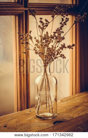 Dry field wild flowers in a vintage glass bottle on an aged wood table by a georgian window selective focus toned