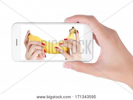 Woman using her smart phone searching sexy hand red nails holding banana. men's health and penis size sexual concept Isolated on white background.