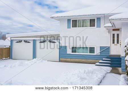 Entrance of residential house with front yard in snow. Beautiful North American house with double garage on winter cloudy day