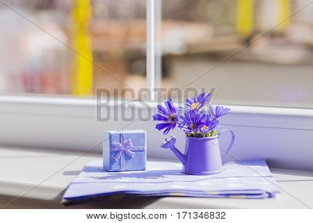 Little Watering Can With Spring Flowers Bouquet Near The Window