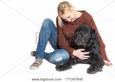 Studio shot of blond middle aged woman sitting with the Giant Black Schnauzer dog on the white background. The womnan is looking at the dog.