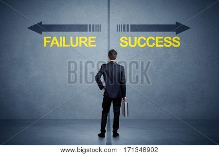 Businessman standing in front of success and failure arrow concept on grungy background