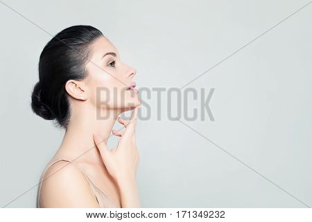 Perfect Young Woman Spa Model with Healthy Skin touching her Hand Her Face. Spa Beauty Facial Treatment and Cosmetology Concept