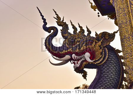 Head's stone serpent king of Nagas with evening twilight sky background in Thai style temple at Rong Sua Ten temple Chiang Rai Province Thailand