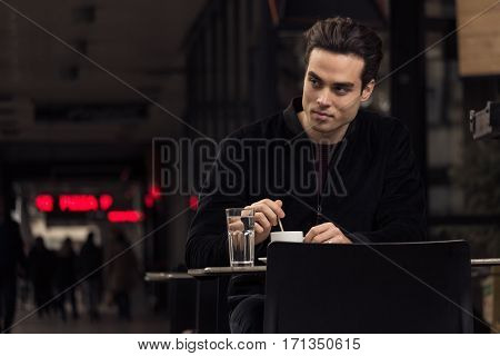 Young Man Stirring Coffe Cup, Outdoors Passersby