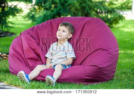 excited kid having fun on bean bag at summer or sping park outdoors.