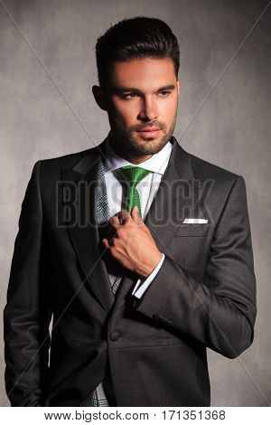 portrait of sexy young man in tuxedo correcting his tie while he looks away from the camera in studio
