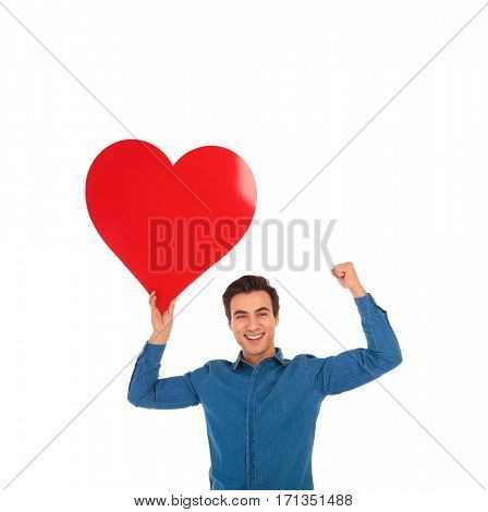 young man holding big red heart is celebrating love with hands in the air on white background
