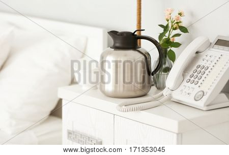 Thermos with coffee on bedside table in bedroom