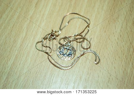 Gold jewelry Libra Astrology old fashion on wooden table