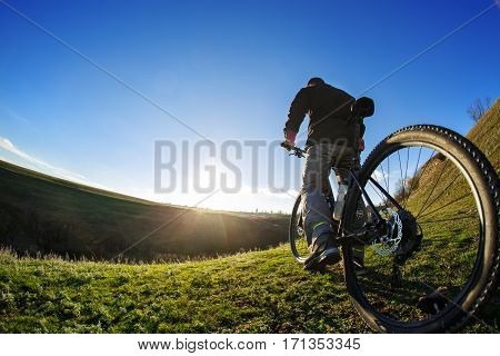 back view of a man with a bicycle against the blue sky. cyclist rides a bicycle. Rear view people collection. backside view of person. blue sky background and mound. Spring season. Green grass.