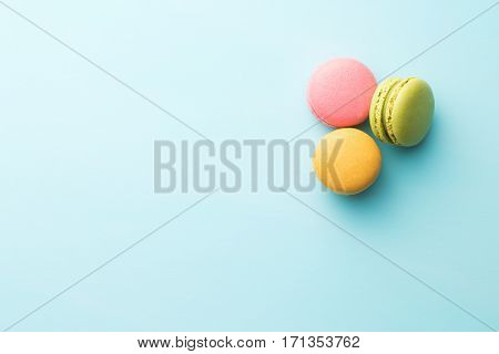 Tasty sweet macarons. Macaroons on blue background. Top view.