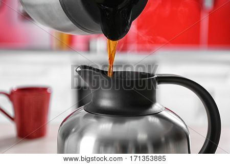 Pouring coffee into thermos kettle,  closeup