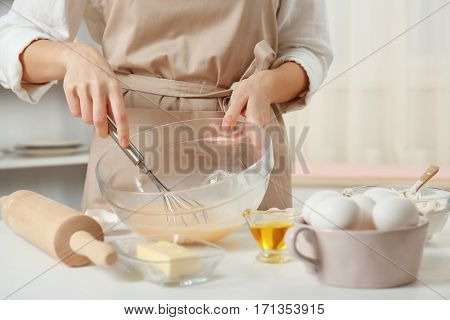 Woman making dough for a pie in a glass bowl