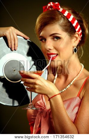 Retro woman with music vinyl record. Pin up girl drink martini cocktail . Pin-up retro female style. Girl wearing red dress drinking beverage through straw.