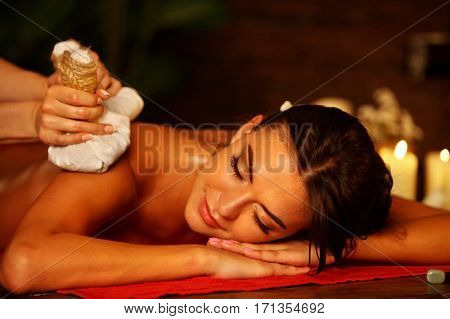 Massage of woman in spa salon. Girl on candles background in massage spa salon. Luxary interior in oriental therapy salon. Close up of female massage hands give herbs hot ball therapy.
