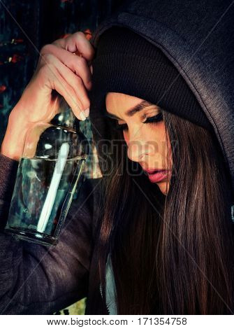 Woman alcoholism is social problem. Female drinking is cause of nervous stress . She in hood and hat drinking alcohol in bad mood and not looking camera. Black background as symbol of mourning.