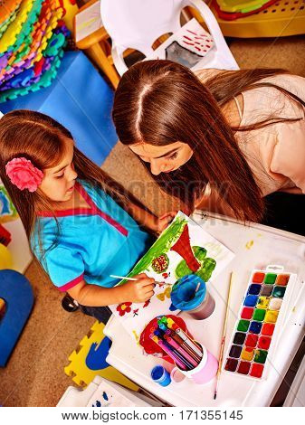 Child painting and drawing in kids club. Craft lesson in primary school. Kindergarten teacher who smiling help small student. Kid girl coloring picture on table in class. Top view.