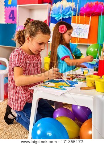 Small students girl painting in art school class. Child drawing by paints on table. Portrait of little girl in kindergarten. Craft drawing education develops creative abilities of children. Group