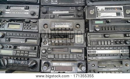Old car cassette radios stacked on top of each other on the shelves in car service.