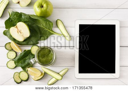 Detox cleanse drink, green smoothie ingredients. Natural, organic healthy juice in glass jar for weight loss diet or fasting day. Cucumber, apple, lime and spinach mix on white wood, top view