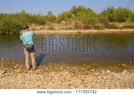 The young man is fishing. Active rest on the nature.