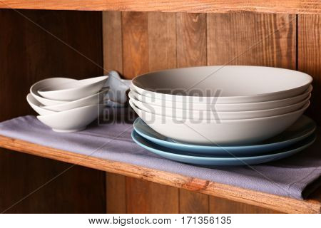 Wooden shelf with white and blue dishes