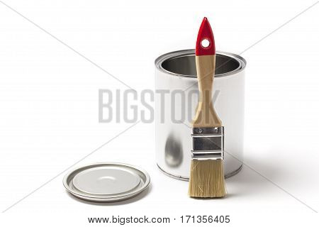 Brush leaning on an open blank metallic tin paint can isolated on white.