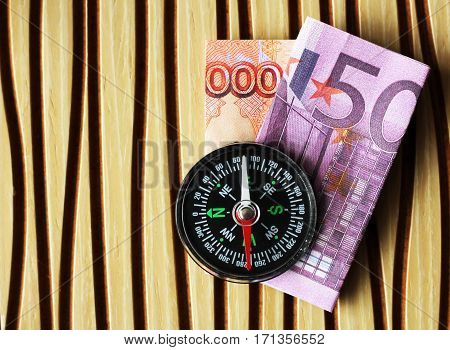 Money and compass for travel on a wooden background