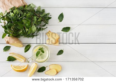 Detox cleanse drink, natural lemonade ingredients. Organic healthy juice in glass jar for weight loss diet or fasting day. Mint, lemon and ginger mix on white wood, top view with copy space