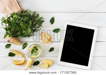Order online detox cleanse drink, natural lemonade ingredients. Organic healthy juice in glass jar. Mint, lemon and ginger mix. With tablet pc screen for copy space, top view