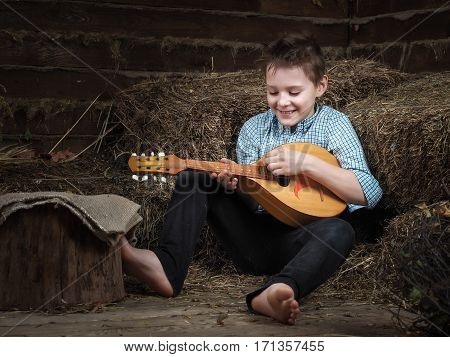 Happy barefoot boy with a mandolin. The teenager plays a musical instrument. Old village house barn