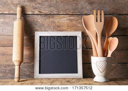 Kitchen utensils and blank blackboard on wooden background