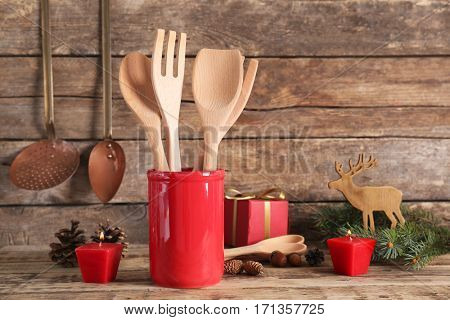 Cooking utensils with decorations on wooden background