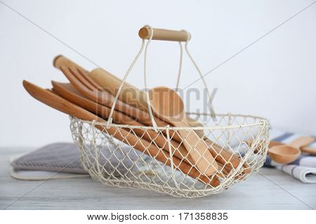 Wooden cooking utensils in basket on table