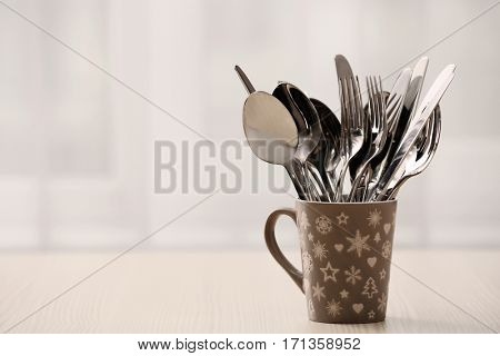 Set of metal kitchen utensils in ceramic cup, on table
