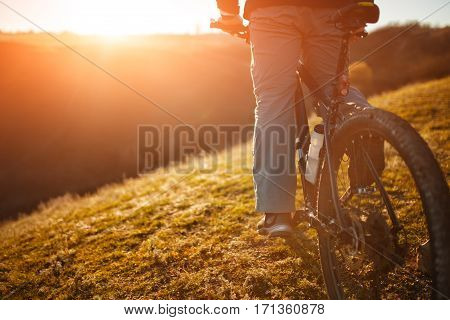 Closeup of cyclist man legs and hands riding mountain bike on outdoor trail in nature. Beautiful landscape. Field with green grass. Spring season. Sunset. Detail of bicycle. Wheel and bicycle seat.