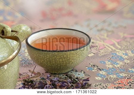 cup with tea on a beautiful tablecloth and a pinch flower tea