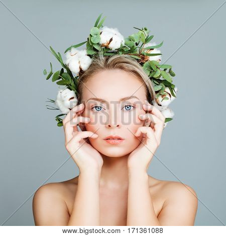 Perfect Girl in a Wreath of Green Leaves and Cotton Flowers. Spa Woman with Healthy Skin